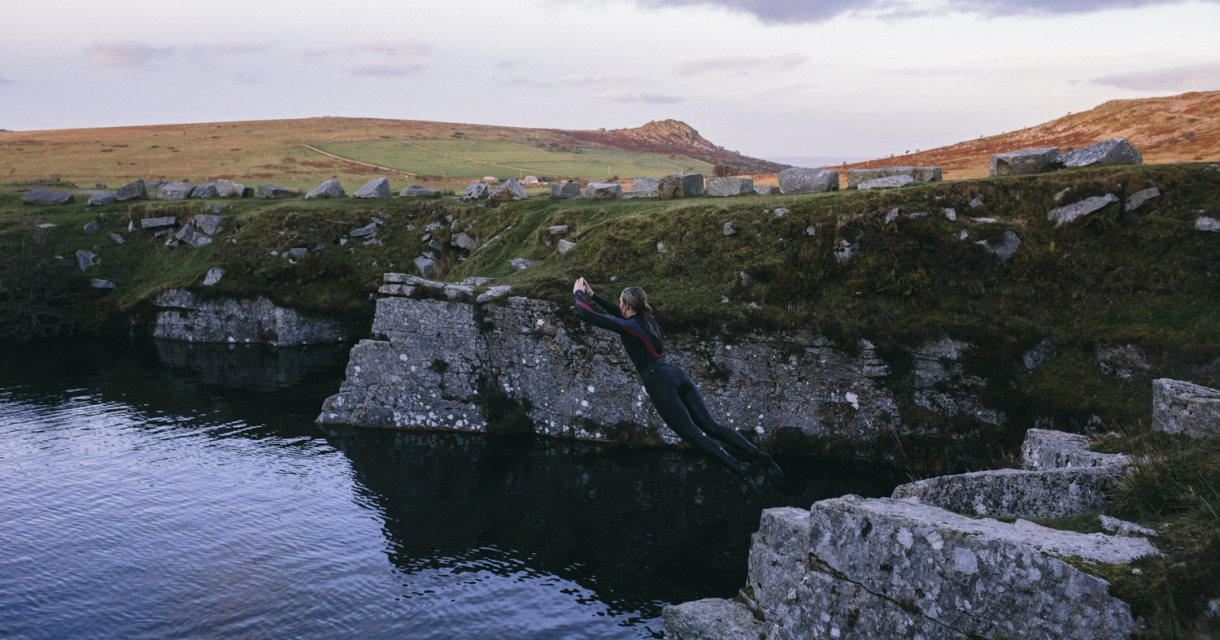 Student in wetsuit jumping from wall into the water.