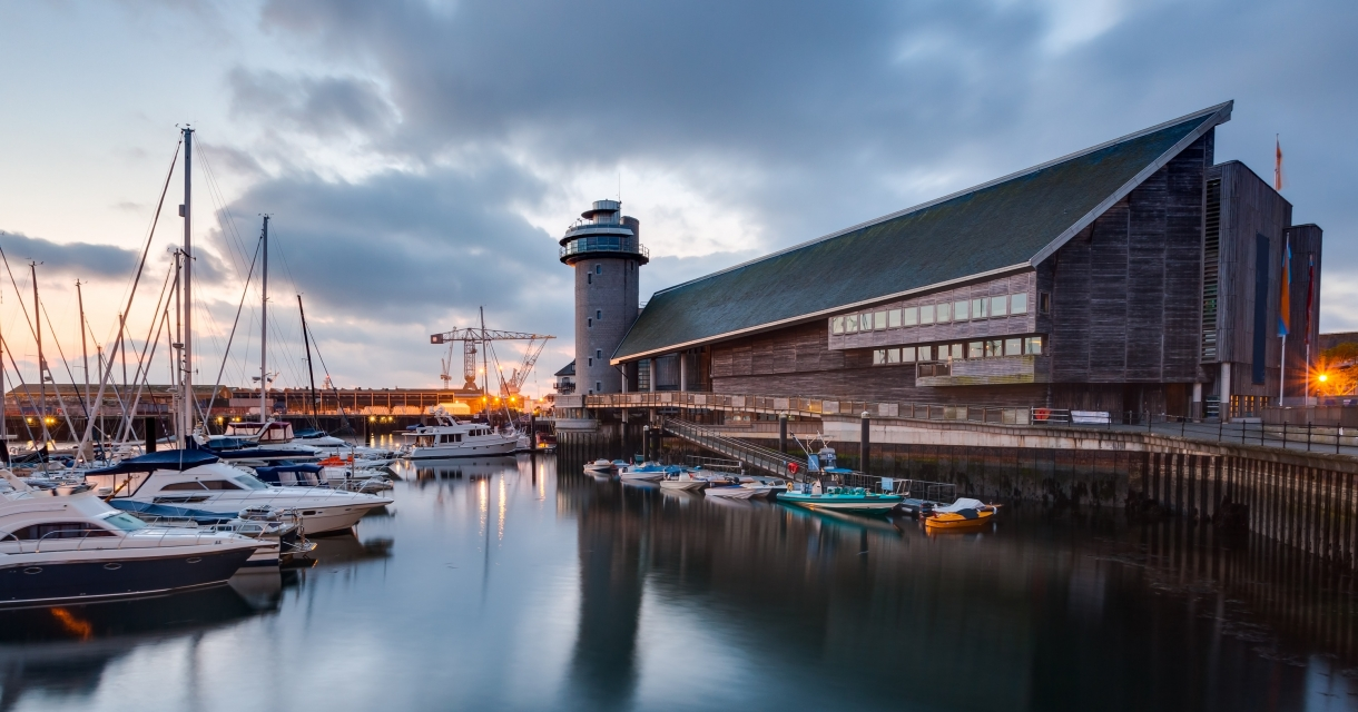 View of wooden clad Maritime Museum next to Port Pendennis harbour filled with boats.