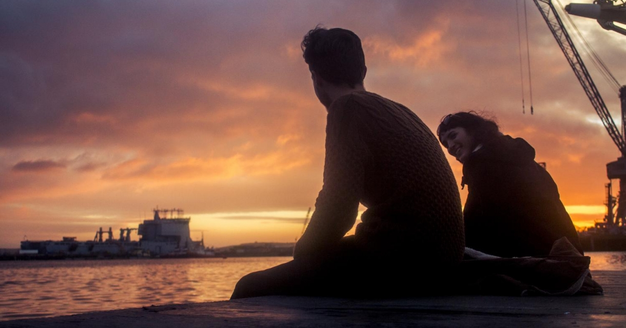 Falmouth students sat on harbour wall looking out to ship and sunset.