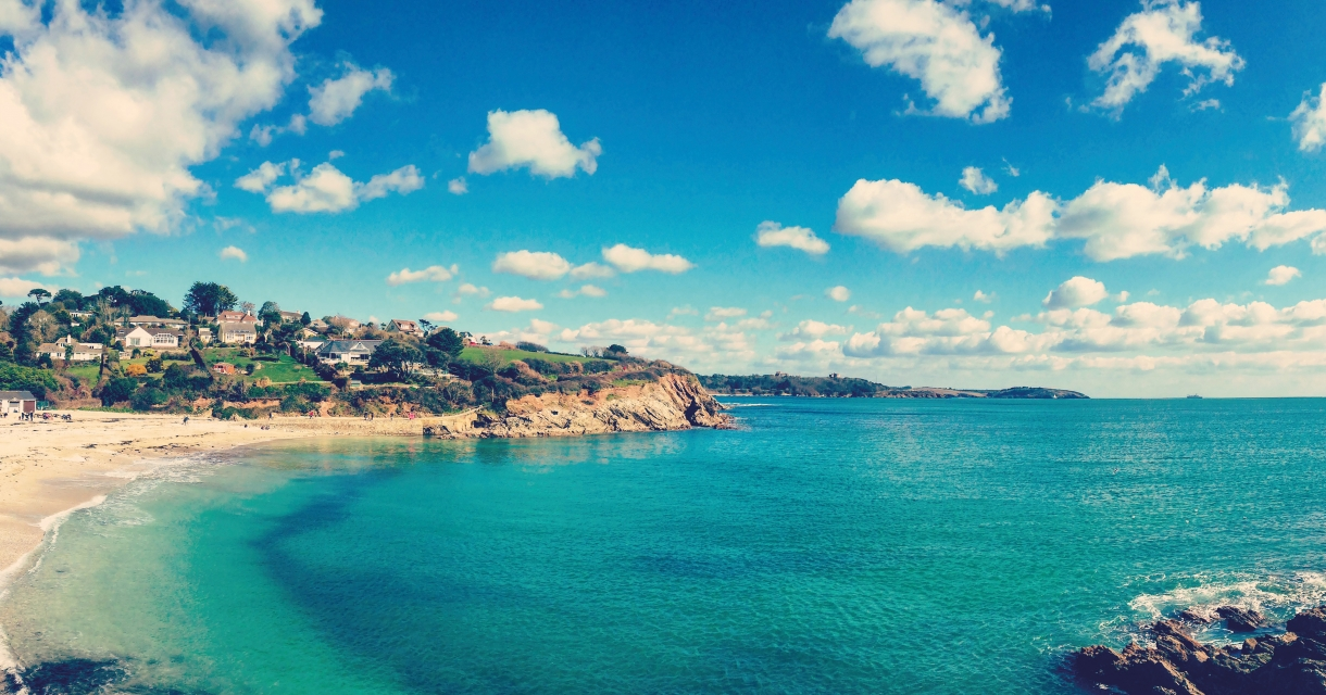 View over the sea at Swanpool beach, turquoise water, bright blue sky and fluffy coulds.