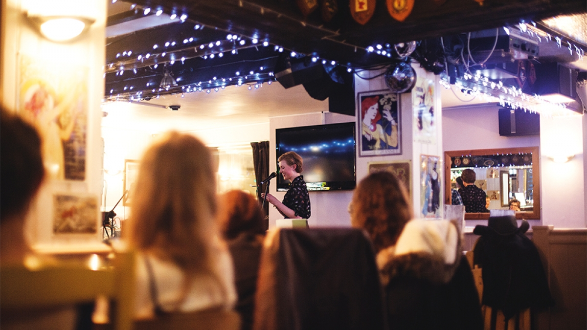 Student speaking into microphone at event in pub surrounded by blue fairy lights.
