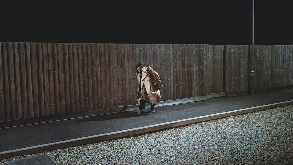 Shot of model wearing a coat over her shoulders on a pavement at night.