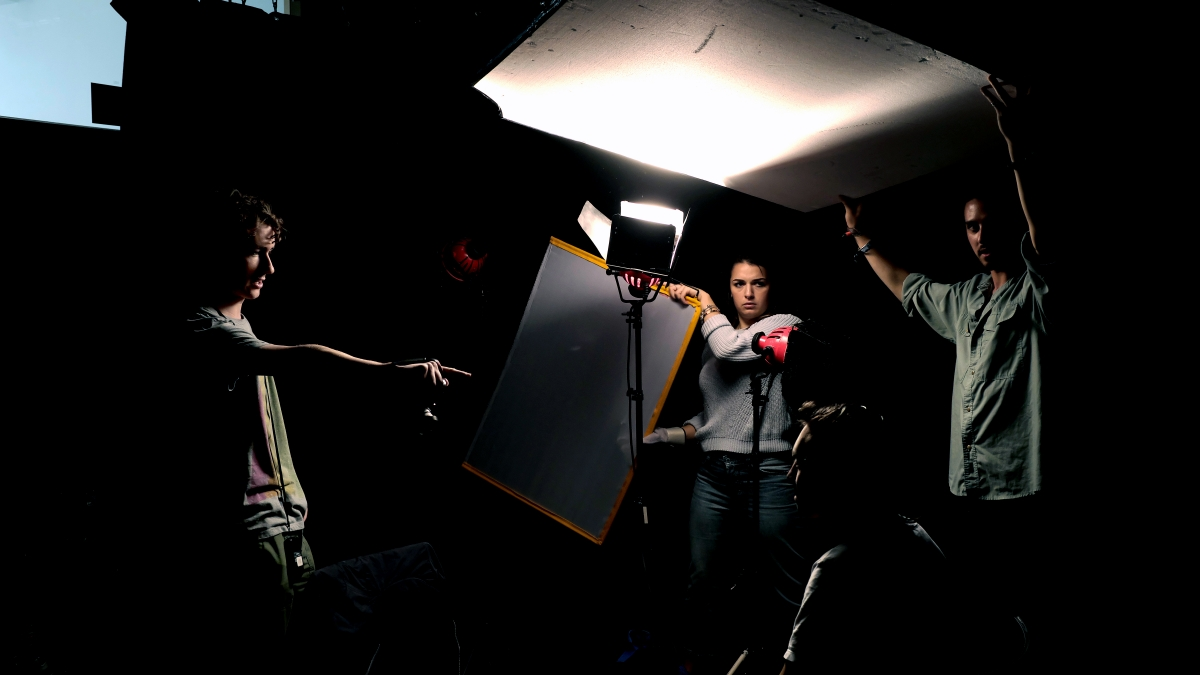 Falmouth film students holding up reflectors  in dramatically lit studio.