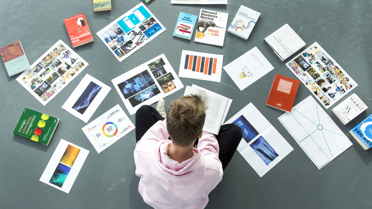 Student sitting cross legged with work laid out around him