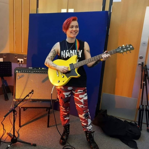 Harri Betsworth performing with her guitar