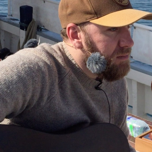 John Lamb singing on a boat for his latest album.