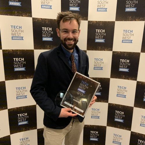 Lecturer holding the Tech South West Award, with a backdrop with branding on it.