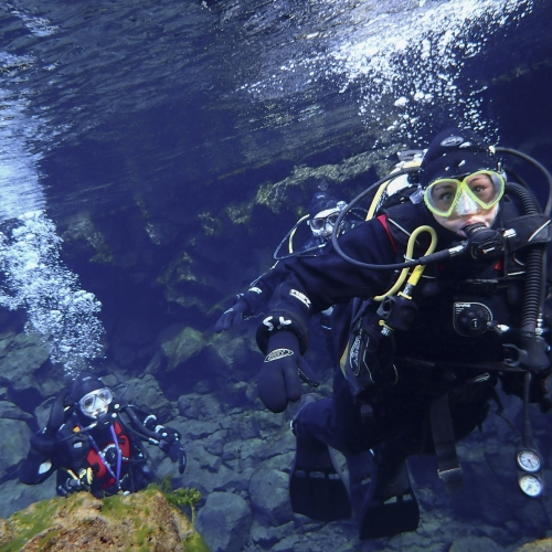 Two students in diving gear under water, bubbles coming out of mouthpiece.