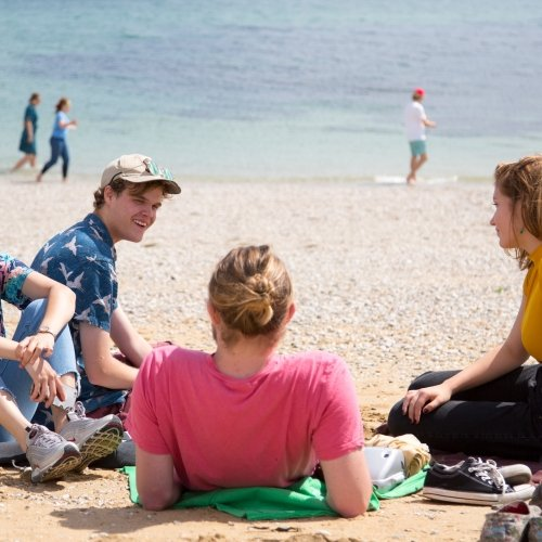 Students relaxing on beach.