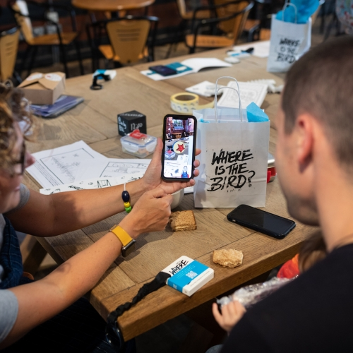 two people at a table looking at a phone