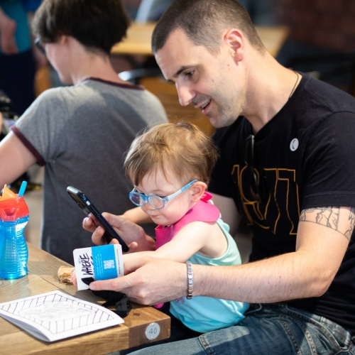 A man with a toddler on his lap with a phone