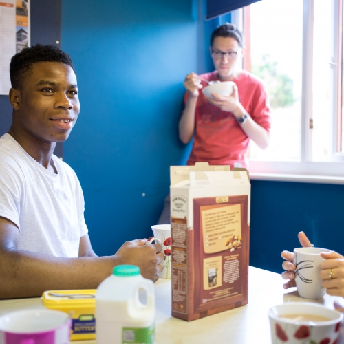 Students eating cereals in blue room.