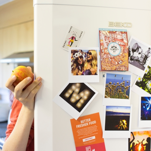 Hand with apple holding open fridge door with photos on it.