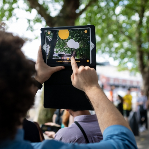 A man holding up an iPad in a street with trees