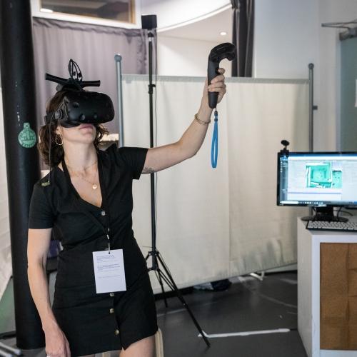 A woman in a black dress wearing a VR headset