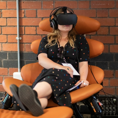 A woman sitting in an orange chair with VR headset on