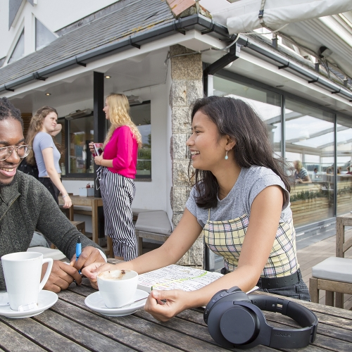 Male and female student talking at a bench with coffee cups and headphones
