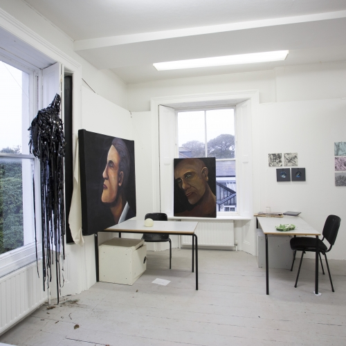 Art studio interior on Falmouth campus with two large painted portraits.