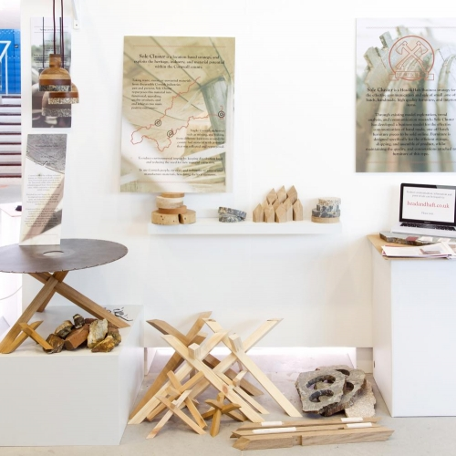 Exhibition with wood sculptures, lights and table.