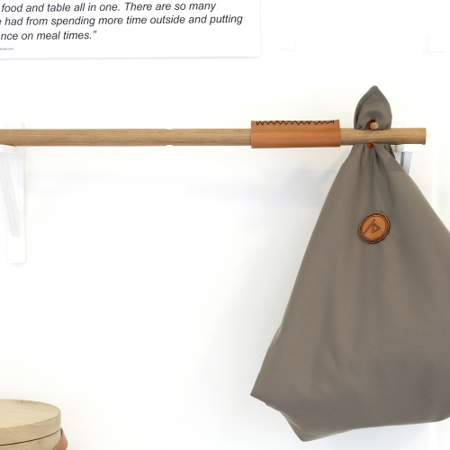 Folded picnic blanket on end of a carrying stick.