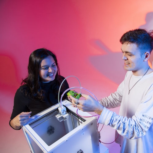 Male student and female student playing with a white box and a green robotic device