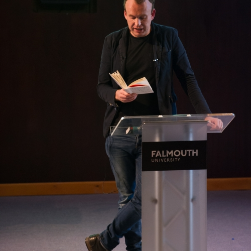 Writer, Matt Haig, reading from book on stage.