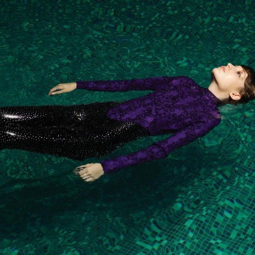 Model floating on back in pool in purple and black wetsuit.