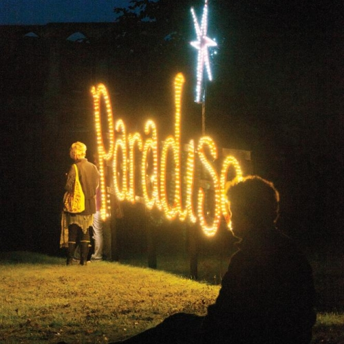 The word paradise illuminated in lights at Port Eliot Festival.