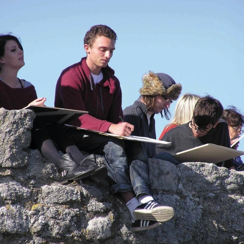 Students sat on stone wall drawing on laps.