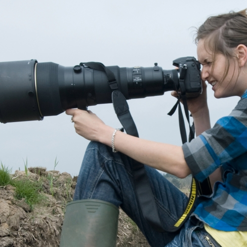 Student in wellies and holding camera with very large lens.