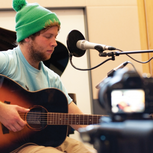 Student in green bobble hat playing guitar into microphone in studio.