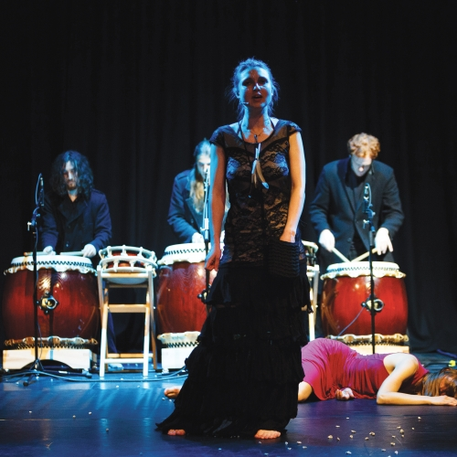 Actor in long black dress, body on the stage floor behind her and 3 drummers at the back of the stage.