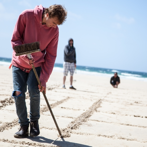 Student on beach drawing into sand with end of a broom.