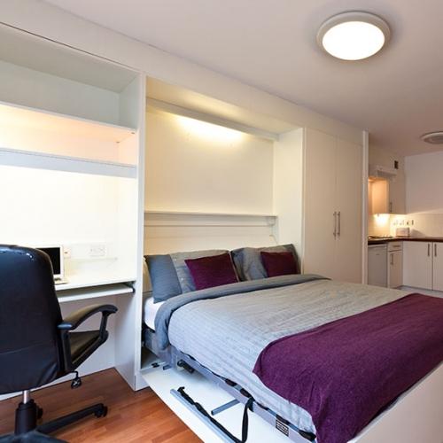 Bedroom studio interior with grey bedspread, purple cushions, and washing machine