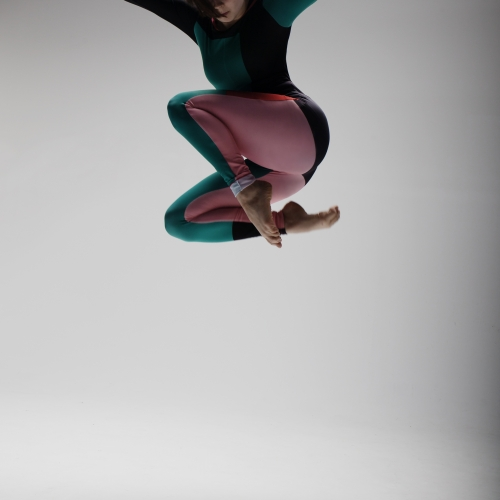 Dancer jumping high with arms spread and legs tucked under in grey backdrop studio.