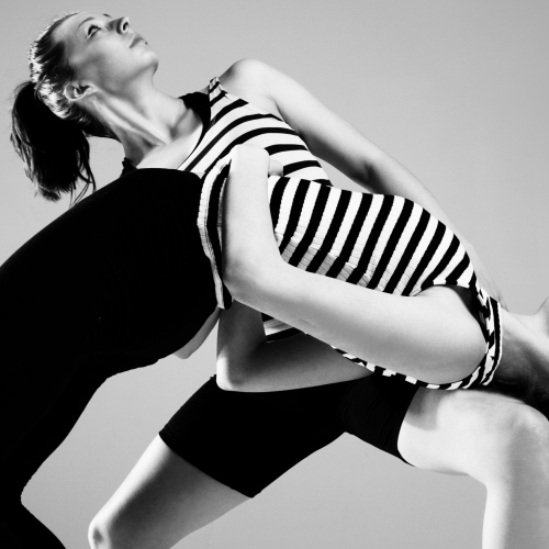 Two female dancers arched and leaning backwards with stripy vests, black and white image.