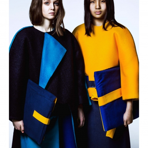 Models in structured outfits of navy, yellow and blue.