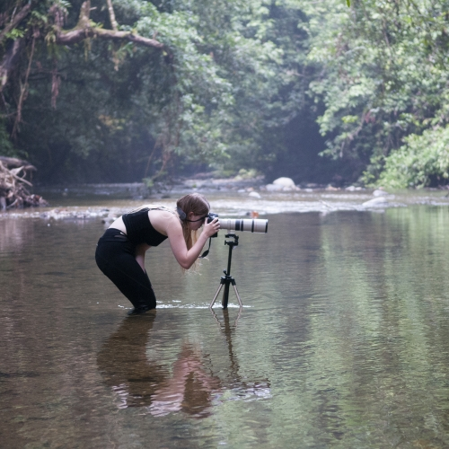 Student immersed up to knees in river bending down to view though camera on tripod.