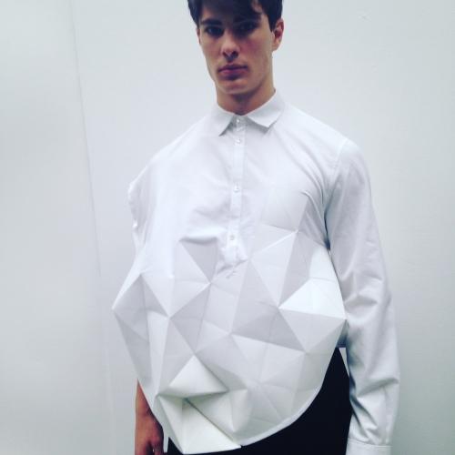 Model wearing white origami folding shirt.