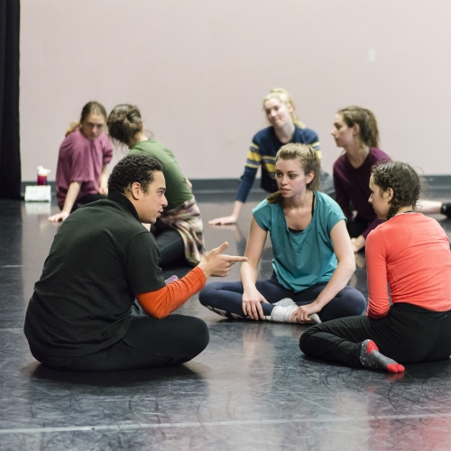 Group of theatre students sat on floor and discussing.