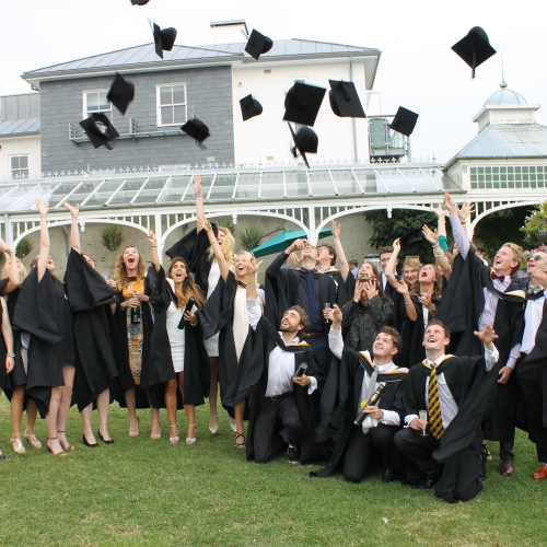 Creative Events Management students graduating and throwing mortar boards into the air