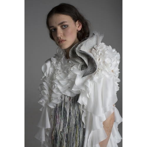 Model wearing white and grey frilly shirt with tassels at the front.
