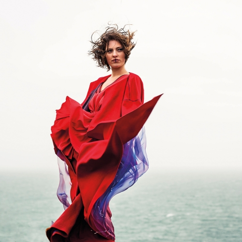 Model posing by sea, red outfit and hair blowing in the wind.