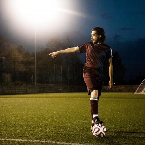 Footballer in dark red kit, pointing and foot stopping the ball.