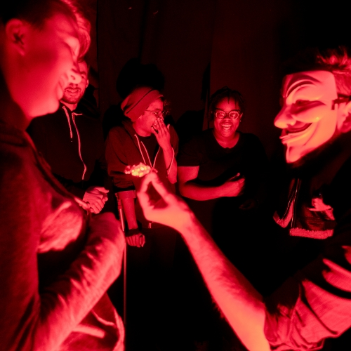 Guests in a red light with masks at Cirque de Terror event