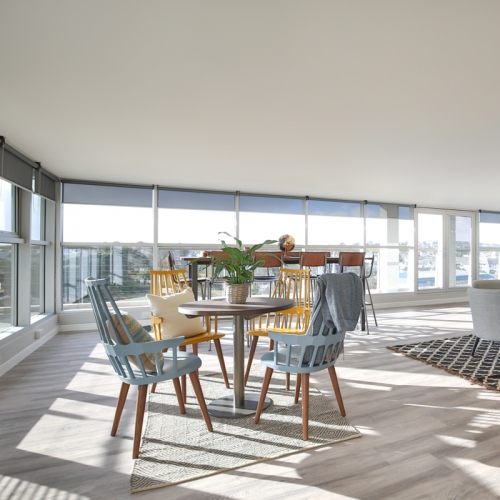 Glass fronted living space with dining table and chairs