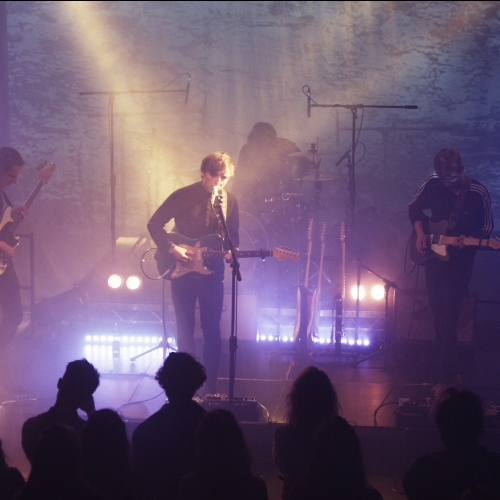 Band with guitarists and drummer on stage with blue and purple lights.