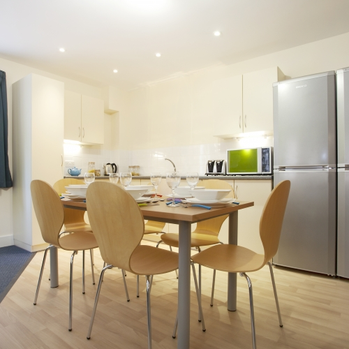 The Sidings kitchen with two double fridges, dining table and cupboards