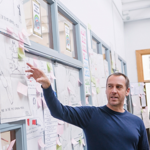 Creative advertising lecturer pointing to ideas wall