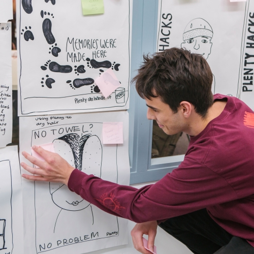 Creative Advertising student sticking Post-it on ideas wall